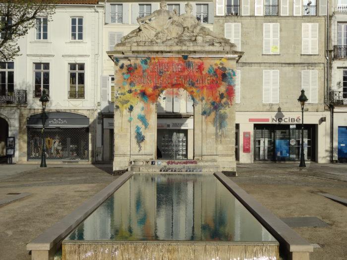 """Fontaine de la place Colbert à Rochefort ornée d'une broderie géante comme un tag Teste """"Eaux de vie sous les eaux bues"""""""
