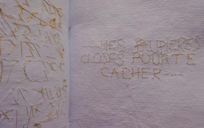 Gros plan sur texte brodé au fil d'or sur carnet blanc