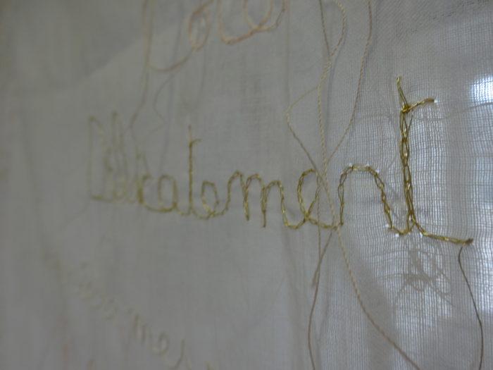 """gros plan sur le mot """"Délicatement"""" brodé en fil d'or sur baptiste de coton blanc"""