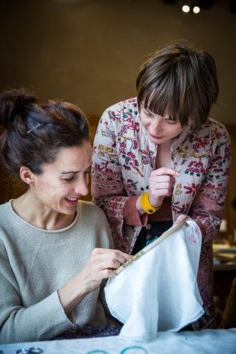 l'artiste donnant des conseils à une femme tenant un tambour à broder. Elles sourient.