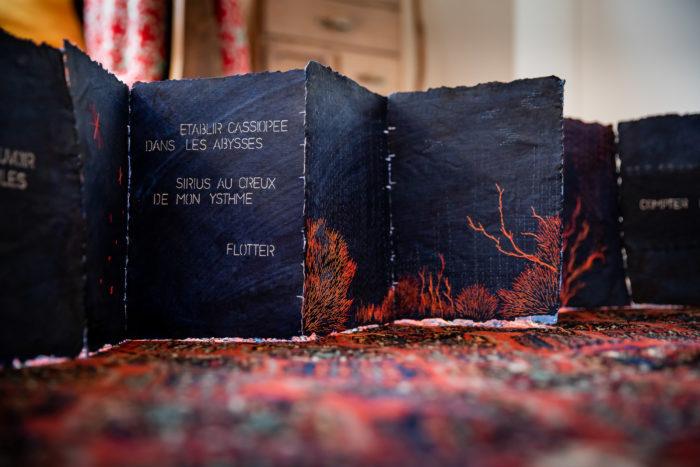 """Livre bleu indigo brodé en orange avec texte """"Etablir Cassiopée dans les abysses, Sirius au creux de mon Ysthme. Flotter"""""""