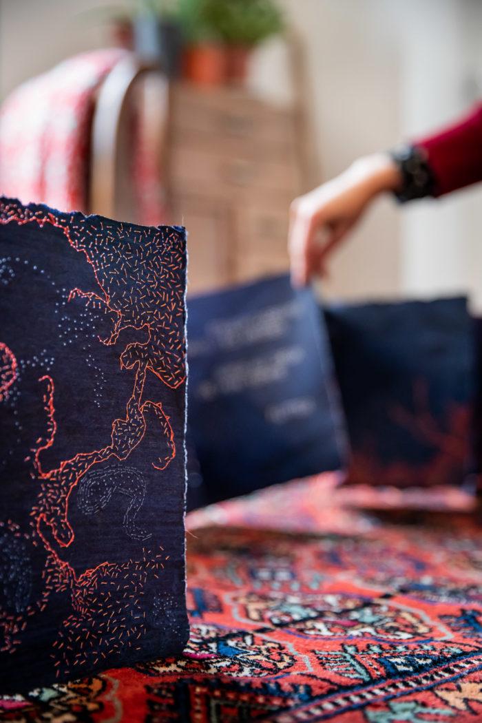 Gros plan sur une page du livre bleu indigo brodé en oragne. La lumière passe à travers les trous laissés par l'aiguille.