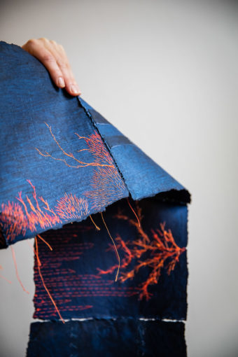 main tenant le livre indigo brodé en orange. Broderie au motif végétal, des fils pendent à la manière de racines