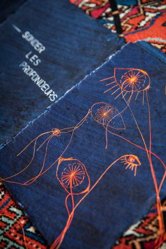 """double page du livre indigo brodé en orange. Broderie d'oeils de différentes taille, fils libres commes des tentacules. Texte en blanc """"sonder les profondeurs"""""""