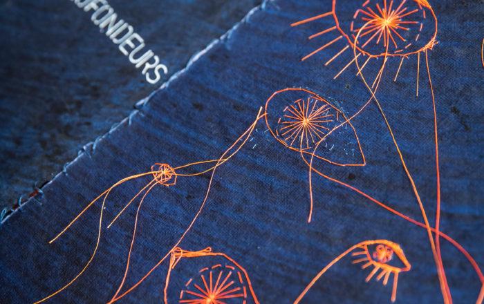 double page du livre indigo brodé en orange. Broderie d'oeils de différentes taille, fils libres commes des tentacules. Texte en blanc
