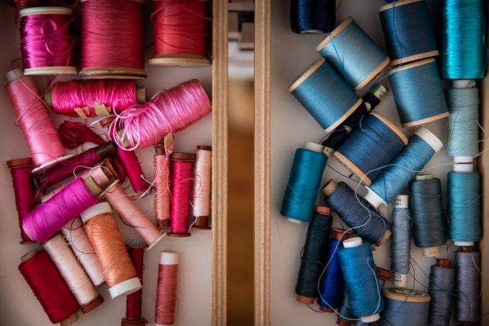 deux tiroirs de bobines rangées par couleur: un tiroir rose, l'autre bleu.