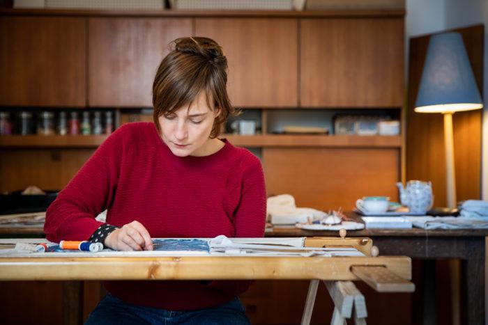 l'artiste brodant sur métier dans son atelier. Tons bleus et rouges