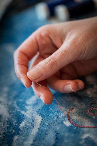 gros plan sur la main de l'artiste brodant un fil orange sur un tissu bleu