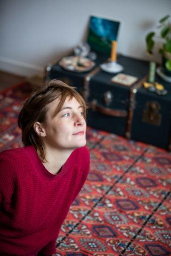 Portrait femme pull rouge assorti au tapis sur lequel elle est assise