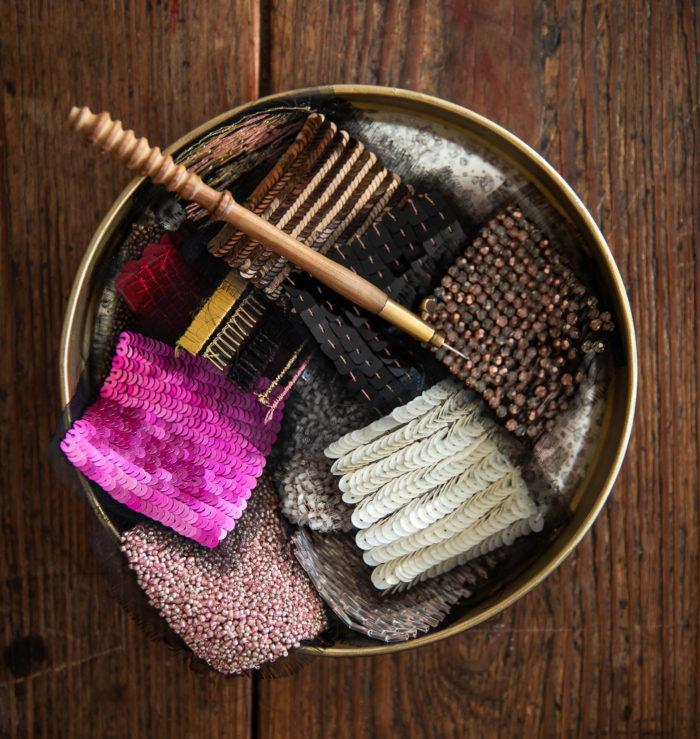 petit plateau rond présenant des échantillons de broderie de perles et paillettes. Crochet de Lunéville