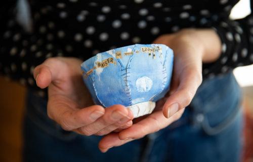 Main tenant un bol en papier brodé bleu avec des lettres découpées dans des journaux anciens. On distingue le mot