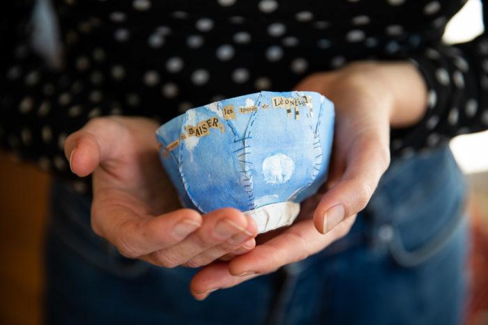 """Main tenant un bol en papier brodé bleu avec des lettres découpées dans des journaux anciens. On distingue le mot """"Baiser"""""""