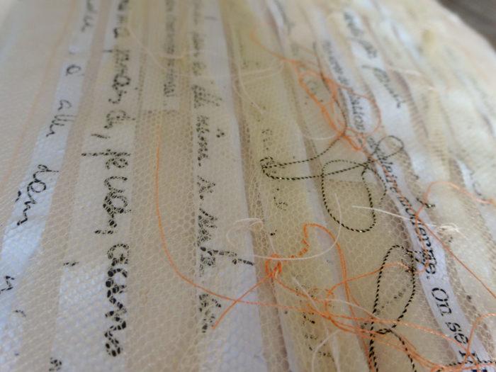 détail sur des bandes de textes insérées dans du tulle de soie et brodées. Tons blans, écru, corail et noir