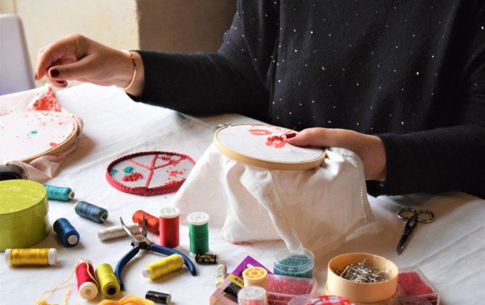 gros plan d'un atelier broderie: fournitures au preimer plan, des mains aux ongles vernis tiennent un tambour à broder
