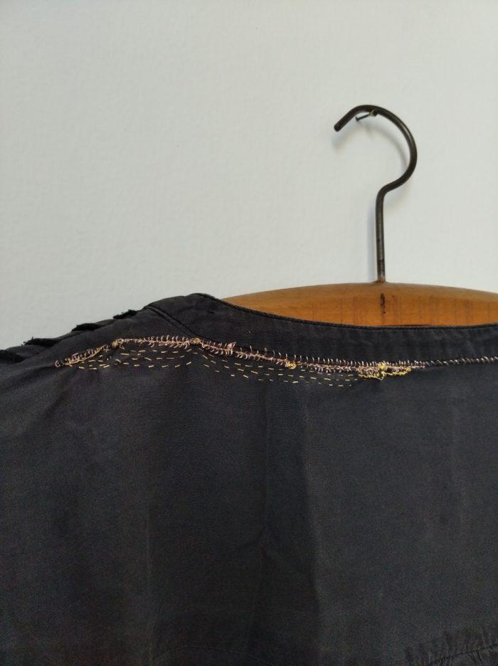détail d'un vêtement réaré au fil d'or pendu sur un cintre. La broderie est formée de petits points irréguliers