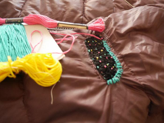 Détail d'un vêtement en train d'être réparé: application de tissu avec point de feston. Tons acidulés rose, jaune, turquoise