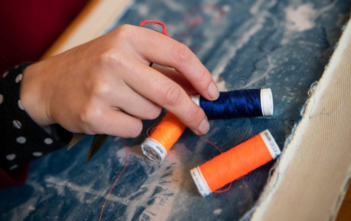 main, tissus bleu, fils orange fluo